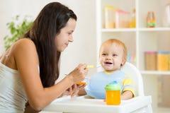 Cuchara de la madre que alimenta a su niño Imagen de archivo
