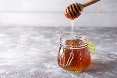 Cuchara de la miel con el tarro en un fondo ligero Imagenes de archivo
