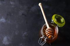Cuchara de la miel con el tarro en un fondo negro Fotos de archivo
