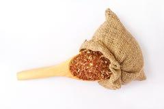 Cuchara de madera con arroz rojo Imágenes de archivo libres de regalías