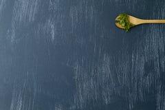 Cuchara de madera con cilantro fresco en fondo azul imagenes de archivo