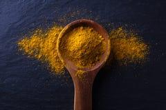 Cuchara de madera con el polvo de curry Foto de archivo