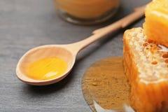 Cuchara de madera con la miel en fondo gris Fotos de archivo libres de regalías