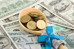 Cuchara de madera con las monedas en un fondo del dinero Foto de archivo libre de regalías