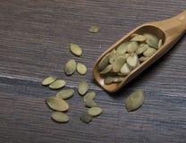 Cuchara de madera con las semillas de calabaza Foto de archivo