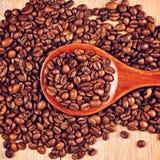 Cuchara de madera con los granos de café Imagen de archivo libre de regalías