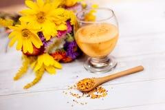 Cuchara de madera con polen y vidrio con el líquido del polen Imagen de archivo libre de regalías