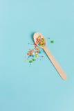 Cuchara de madera de la decoración de Pascua con los ingredientes coloreados del azúcar encendido Foto de archivo