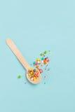 Cuchara de madera de la decoración de Pascua con los ingredientes coloreados del azúcar encendido Imagenes de archivo