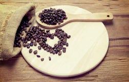 Cuchara de madera de los granos de café pequeña en la madera con el backgroun del corazón Imagen de archivo libre de regalías