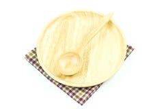 Cuchara de madera en placa de madera en un mantel Imagen de archivo