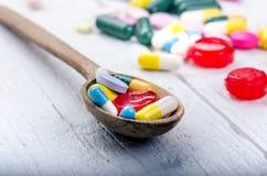 Cuchara de madera llena de tabletas Fondo de la farmacia en una tabla blanca Tabletas en un fondo blanco Píldoras Medicina y sano Imágenes de archivo libres de regalías