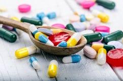 Cuchara de madera llena de tabletas Fondo de la farmacia en una tabla blanca Tabletas en un fondo blanco Píldoras Medicina y sano Fotografía de archivo