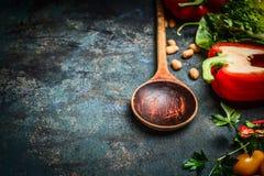 Cuchara de madera vieja y verduras frescas para el vegano sabroso que cocina en el fondo rústico, cierre para arriba Fotografía de archivo
