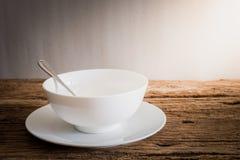 Cuchara de plata en el cuenco blanco y la placa blanca en el tablero de la mesa de madera Imagen de archivo