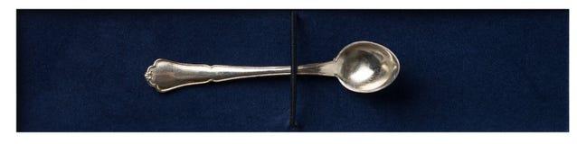 Cuchara de plata en el terciopelo azul Imagen de archivo libre de regalías