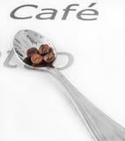 Cuchara de plata y granos de café Foto de archivo libre de regalías