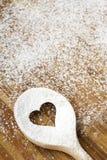 Cuchara del agujero del corazón en el tablero de madera de los pasteles Foto de archivo