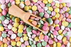 Cuchara dosificadora de madera en la pila de caramelos redondos coloridos Foto de archivo libre de regalías
