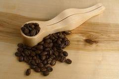 Cuchara dosificadora del café y granos de café en un tablero de madera Imagenes de archivo