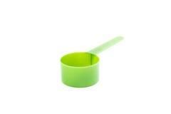 Cuchara dosificadora plástica verde en el fondo blanco Fotografía de archivo