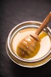 Cuchara en un cuenco de miel en un primer oscuro de la pizarra Imágenes de archivo libres de regalías