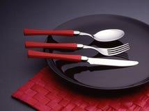 Cuchara, fork y cuchillo en una placa negra Fotografía de archivo libre de regalías