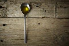 Cuchara por completo del aceite de oliva imagenes de archivo
