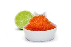 Cuchara roja del caviar y cal unfocused imagenes de archivo