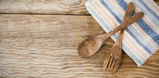 Cuchara y bifurcación de madera con la servilleta en la tabla Imagenes de archivo