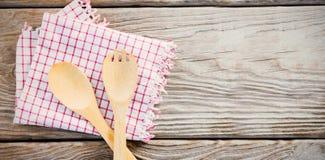 Cuchara y bifurcación de madera con la servilleta en la tabla Imagen de archivo
