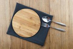 Cuchara y bifurcación de madera de bambú en blanco de la tabla de cortar Imagen de archivo libre de regalías