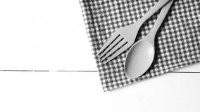 Cuchara y bifurcación de madera en color de tono blanco y negro de la toalla de cocina Fotos de archivo