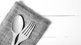 Cuchara y bifurcación de madera en color de tono blanco y negro de la toalla de cocina Fotografía de archivo libre de regalías