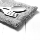 Cuchara y bifurcación de madera en color de tono blanco y negro de la toalla de cocina Fotografía de archivo