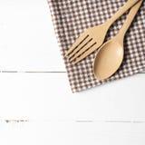 Cuchara y bifurcación de madera en la toalla de cocina Imagen de archivo libre de regalías