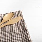Cuchara y bifurcación de madera en la toalla de cocina Foto de archivo libre de regalías