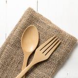 Cuchara y bifurcación de madera en la toalla de cocina Imágenes de archivo libres de regalías