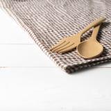 Cuchara y bifurcación de madera en la toalla de cocina Fotografía de archivo