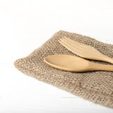 Cuchara y bifurcación de madera en la toalla de cocina Fotografía de archivo libre de regalías