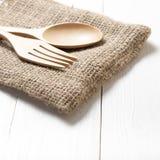 Cuchara y bifurcación de madera en la toalla de cocina Imagen de archivo