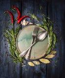 Cuchara y bifurcación en la placa con el marco de las hierbas y de las especias en la tabla de madera azul marino Imágenes de archivo libres de regalías