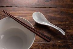 Cuchara y cuenco de cerámica con el shopstick de madera en la tabla de madera Foto de archivo