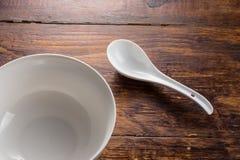 Cuchara y cuenco de cerámica en la sobremesa de madera Imagen de archivo