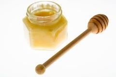 Cuchara y miel en el tarro de cristal en el fondo blanco Imagenes de archivo