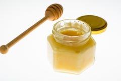 Cuchara y miel en el tarro de cristal en el fondo blanco Foto de archivo libre de regalías