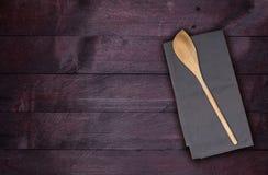 Cuchara y toalla de cocina de madera en el fondo de madera de caoba Fotografía de archivo