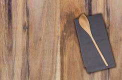 Cuchara y toalla de cocina de madera en la madera del acacia Imagenes de archivo