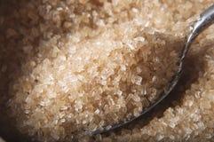 Cucharada de azúcar de Brown en tazón de fuente Foto de archivo