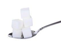 Cucharada de cubos del azúcar Imagenes de archivo